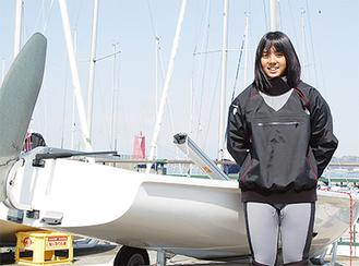 葉山港で420級のヨットと写真に収まる角田さん。今大会では新たなペアで頂点を狙う