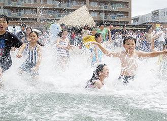 平井市長のカウントダウンで勢い良く海に駆け込む子どもたち