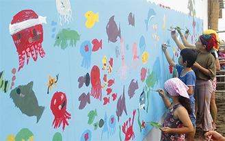 ペンキで思い思いの海の生き物を描く「あとりえうる」の子どもたち。3時間ほどで高さ2m、幅11mほどもある大作の壁画が誕生した。