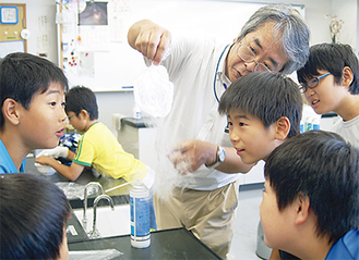 液体窒素につけた二酸化炭素が固体化するのに目を輝かせる児童ら