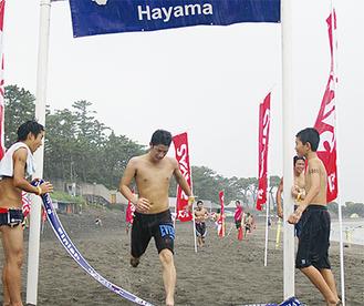 水泳、ボード漕ぎ、ランニングを終えゴールする参加者