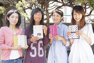 完成した手帳を手に笑顔のメンバー
