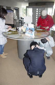地震発生の放送で机の下にもぐる、来庁者扮する職員
