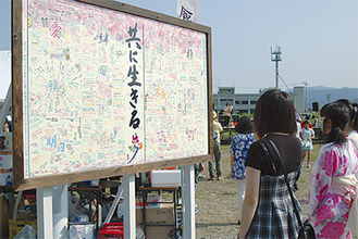 七夕まつりの会場に設置されたボードに見入る陸前高田の中学生