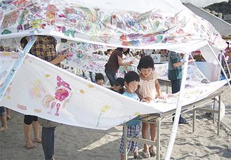 会場で一際目を引いた「世界一長いぬり絵」。会場を訪れた子どもらが鮮やかに彩色し、出展した福岡さんは「作品に命が吹き込まれたよう」と笑顔をほころばせた。