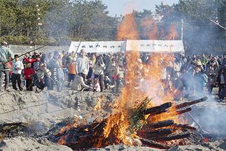 勢いよく燃える炎を見守りながら餅を焼く参加者