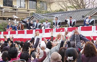 空を舞う福袋に懸命に手を伸ばす市民ら。まき手は年男の平井市長らが務めた
