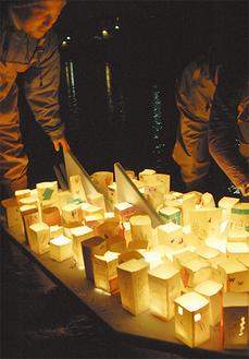 子どもたちが手作りした灯ろうを船に並べる青年会議所メンバー