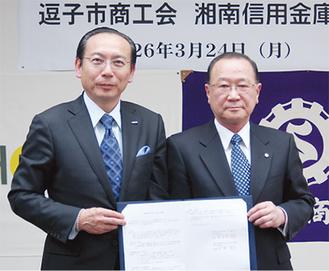 覚書を交わす湊屋会長(右)と石渡理事長(左)