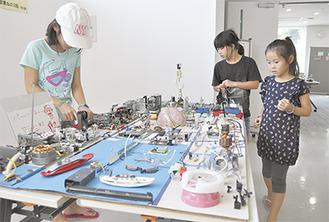 電気機器のパーツを使った作品を見入る子どもら