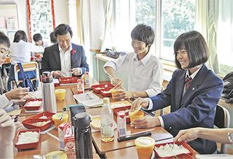 導入初日、平井市長とともに給食を楽しむ生徒ら(=14日、沼間中学校)