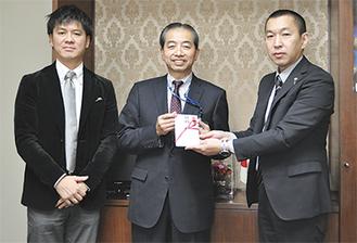 村松教育長(中央)に目録を手渡す野崎副社長。写真左は植田球団代表(=9日、逗子市役所)