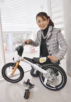 主力商品のランニングバイク「RENNARD(レンラッド)」と川島さん。昨年は約1500台を売り上げた