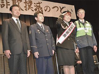 一日署長に委嘱され、敬礼する山田さん(右から2番目)