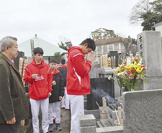 テッド・フルモトさん(左)の父が眠る墓に手を合わせるバンクーバー新朝日軍のメンバー(=9日、横浜 妙香寺)
