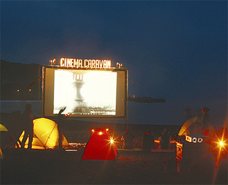 砂浜に設置される300インチの巨大スクリーン(写真は過去/主催者提供)。上映スケジュールやイベント詳細はホームページ(「逗子海岸映画祭」で検索)まで