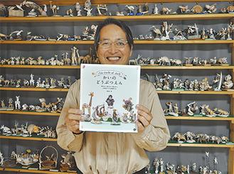 初めての著書を手に笑みを浮かべる角田さん(=9日、堀内の自宅で)。背景はこれまで手掛けてきた「かいのどうぶつ」たち