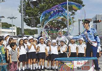 巨大なシャボン玉に歓声をあげて喜ぶ園児ら(=9月29日、逗子駅前広場)