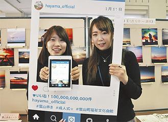 町公式アカウントと写真展をPRする秘書広報係の高野さん(写真右)と笠井さん
