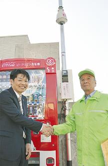 設置された自販機と防犯カメラの前で握手する緑川会長(右)と飯田支店長