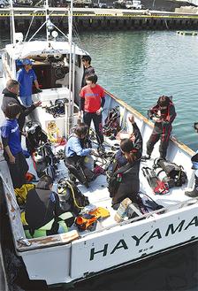 ボートダイビングに向かう船舶で出発の準備をする参加者ら(=21日、真名瀬漁港)