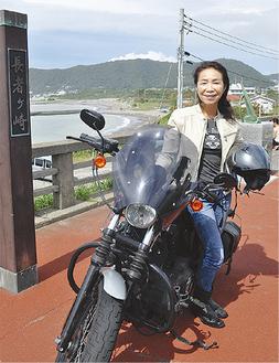 愛車のハーレーダビッドソンと写る松林さん(=9月28日、長者ヶ崎)。バイクツーリング専門の旅行会社は国内では唯一という