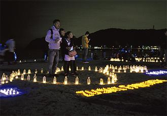 ハート型に設置されたキャンドルで記念撮影する家族客(=10日、逗子海岸)