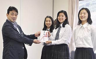 目録を手渡す石井会長(写真左)