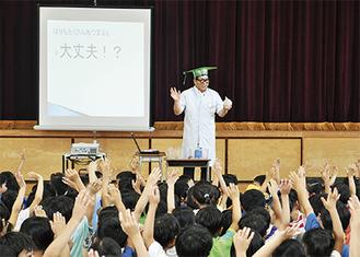 全校児童の前で実験を披露する益田校長(=6日)