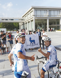 広島平和記念公園に到着し、父寛昭さんとポーズを決める慎人さん(右)=写真は提供=