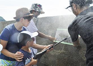 魚の形に切り抜いたアクリル板に高圧洗浄機をかける児童(=先月25日、小坪)
