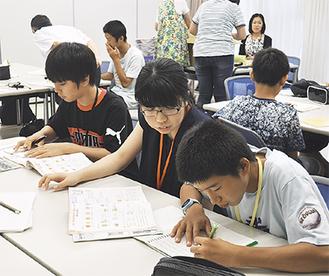 大学生のサポートで学習に取り組む中学生ら(=先月30日、池子)