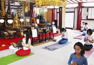 光照寺の本堂でヨガに取り組む参加者(=先月29日、沼間)