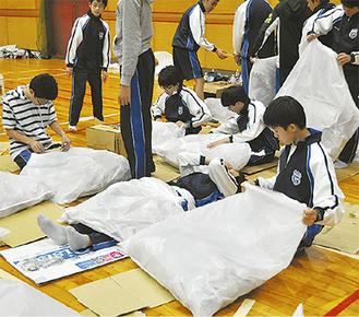 ビニール袋と新聞紙で簡易布団を作る生徒ら