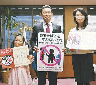 採用された路面標示(中央)。標語とイラストが選ばれた成瀬さん(左)と堀部さん(右)