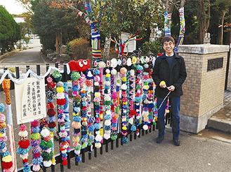 毛糸で作られた飾りつけを手入れするPTA会長の泉さん(=先月24日、池子小)