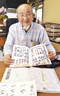「我々の宝物」とこれまでの全出演者が記帳した冊子を手にほほ笑む渡邊さん