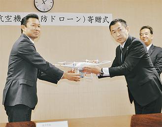 寄贈式で平井市長にドローンを手渡す野崎社長(右)