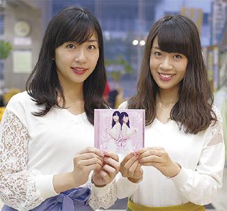 アルバムを手にする姉の華さん(左)と妹の麗さん