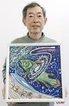 色彩豊かなチョーク画を手にする小菅さん