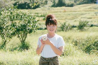 棚田を前にアイスを手にする山口さん(提供写真)