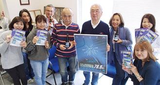 開局記念のポスターを持つ木村会長(右から4人目)とスタッフたち