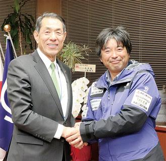 桐ケ谷市長と握手する三浦さん(右=逗子市提供)