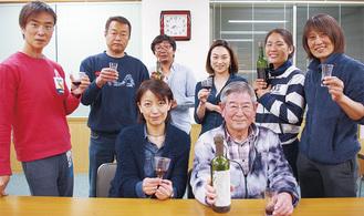 ボトルを手にする角田さん(前列右)と漁協、NANAの関係者たち