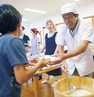 熱々の豆腐を子どもに手渡す亀田さん(右)