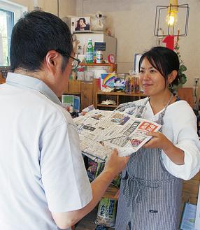利用者から完成品を受け取る堤崎さん(右)