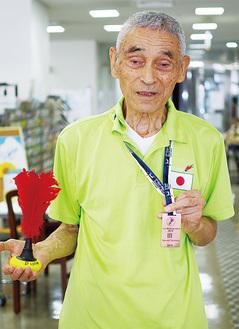競技で使う羽がついたボールとメダルを持つ長谷川さん