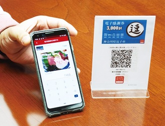 電子感謝券を利用する際のスマホ画面(左)と店が置くQRコード