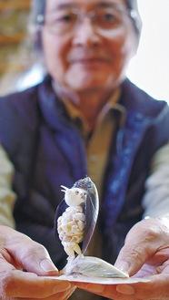 体長は約7cm。菱形の目はウニのとげ、髪の毛はカラスガイで表現した