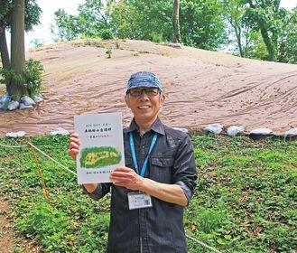 第1号墳の前で冊子を持つ浜野会長